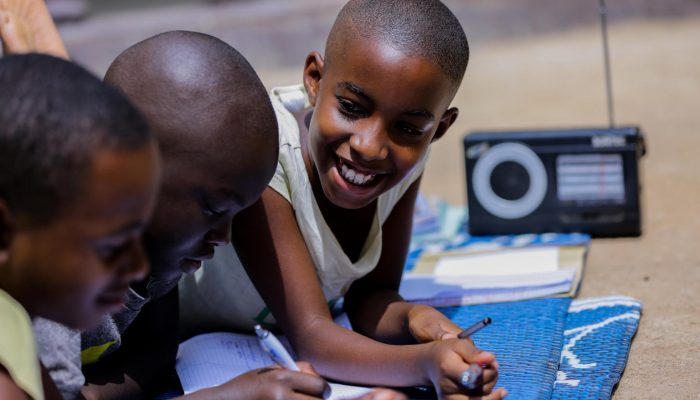"""Children like Dative, Kevin and Merveille listen to radio lessons at home while their primary schools are closed to prevent the spread of COVID-19.   **********  On 15 March, the Government of Rwanda recommended that all schools to prevent the spread of Coronavirus. These closures have been extended to at least late April, with over 3 million of students now out of school and expected to learn at home.   **Finding rapid solutions**  Every lost day of learning can have detrimental impact on a child's future. Rwanda's students needed immediate solutions to help them learn from home.   """"Radio is the most popular and accessible medium in Rwanda. As the national public broadcaster, Rwanda Broadcasting Agency's radio stations reach almost 99 per cent of the population, including Radio Rwanda and five regional stations,"""" says Aldo Havugimana, Director of Radio with Rwanda Broadcasting Agency. """"Given this expansive reach, radio lessons were identified as the most suitable immediate solution.""""  To begin, UNICEF utilised its network and expertise to leverage 144 radio scripts from other countries on primary level literacy and numeracy lessons. These lessons were then contextualised and adapted for Rwanda. UNICEF then leveraged its existing partnership with the national NGO Inspire, Educate, Empower (IEE) and Rwanda Broadcasting Agency to produce and air these scripts throughout the country.  **Developing new radio lessons for students**  With short-term measures in place to ensure learning opportunities for students, UNICEF is now supporting radio material that is aligned with the Rwandan curriculum.    In collaboration with various development partners and Rwanda Education Board, UNICEF continues to support the production and airing of new radio material.  UNICEF is particularly concerned that early learning opportunities are sustained, therefore developing radio content for pre-primary.    """"This lockdown is necessary to prevent further spread of Coronavirus."""